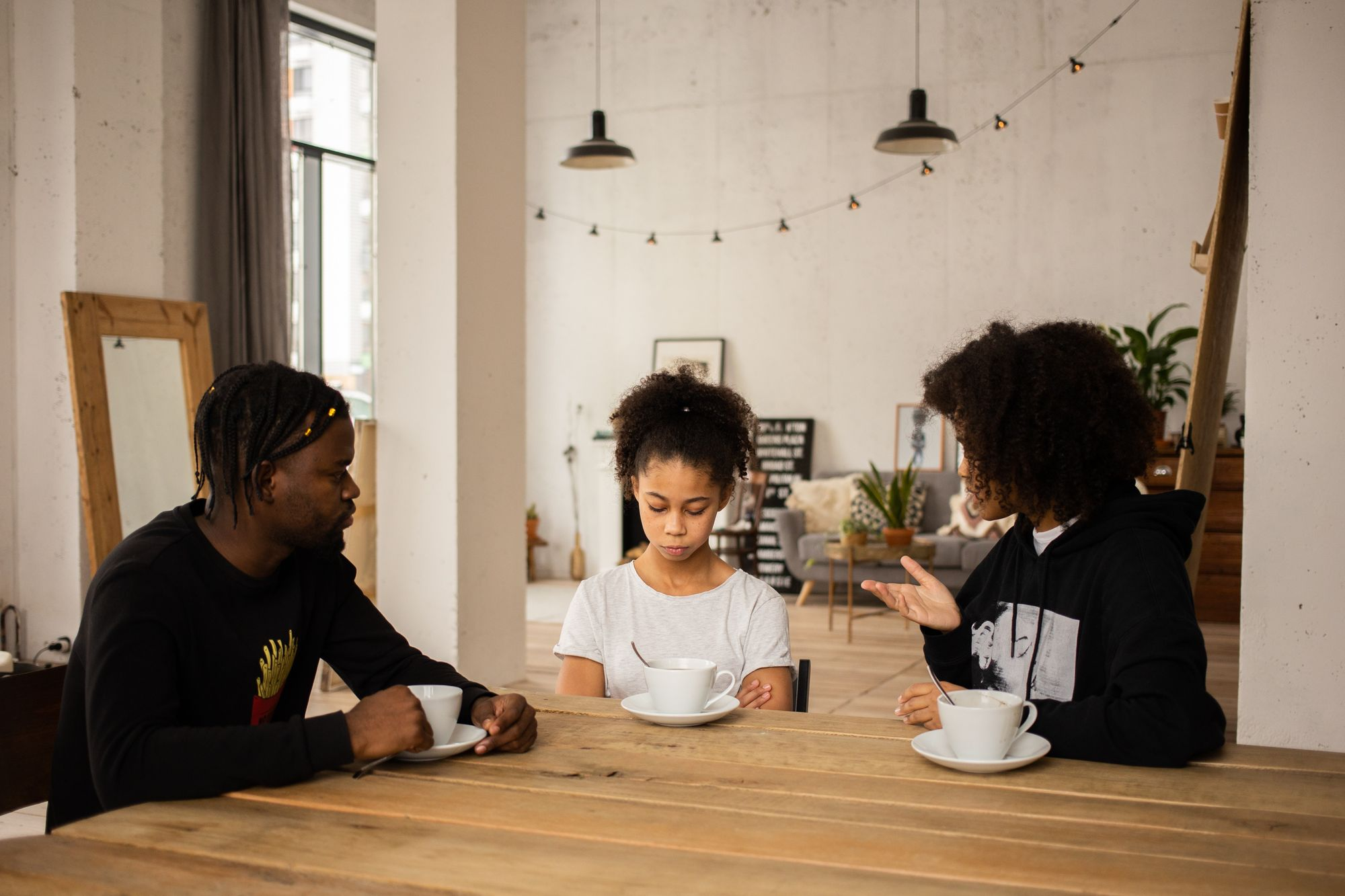 A Black man and Black woman instruct their Black daughter.